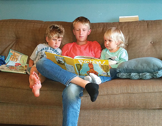 "Submitted photo Dillan DeCock, 12, sits on the couch to read the book ""Pouch!"" by David Ezra Stein to his younger siblings, Simon, 4, and Madeleine, 2. Dillan said he enjoys being homeschooled so he can learn at his own pace."