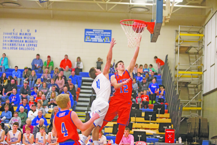 Photo by Sam Thiel Canby's Adam Durfee (12) lays the ball in as Jake Werner (4) of Lakeview defends Monday night.