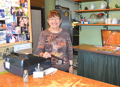 Photo by                  Jody Isaackson Arlene Kanz poses for a photo by the till in her 35-person capacity diner, the Hiway Café, on Division Street in Hendricks. Roast beef or ham dinners are the specials, with a third choice, such as spaghetti with garlic toast.