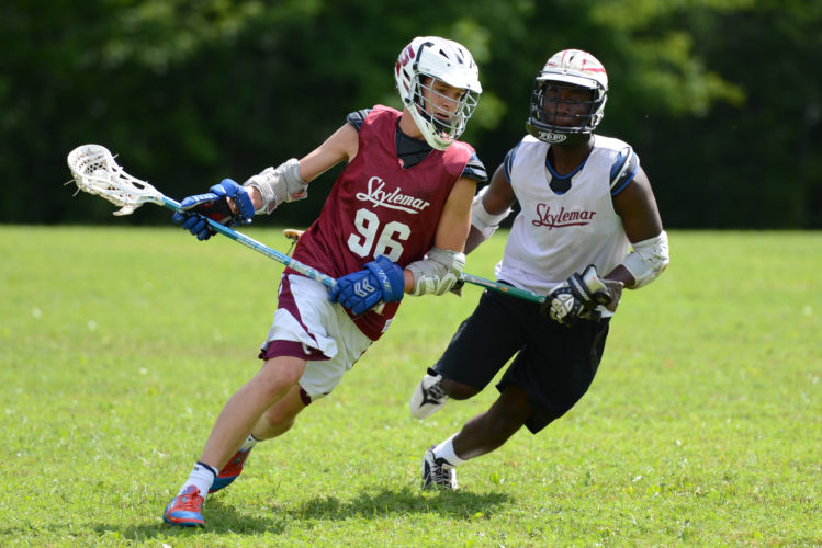 Photo by Shannon Rathmanner In this Aug. 2014 photo, two athletes compete in a lacrosse game at Camp Skylemar in Naples, Maine. Skylemar is a summer sports camp for boys.