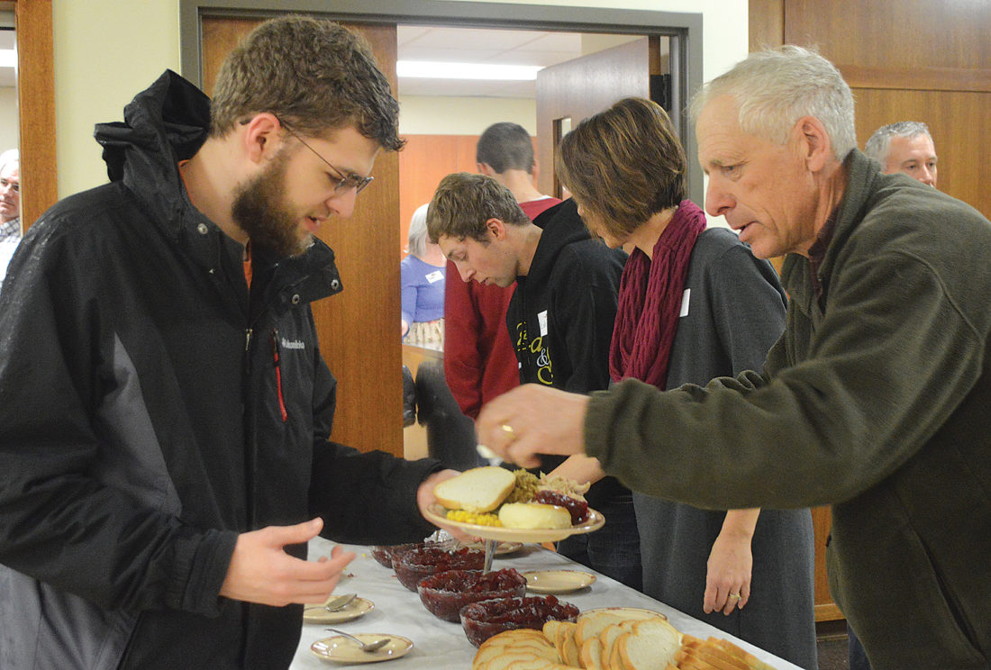 Photo by  Jody Isaackson  Carter Barker of Marshall received a slice of bread from server Mike Sanders at the Community Christmas Dinner at Holy Redeemer's Carlin Hall on Sunday.