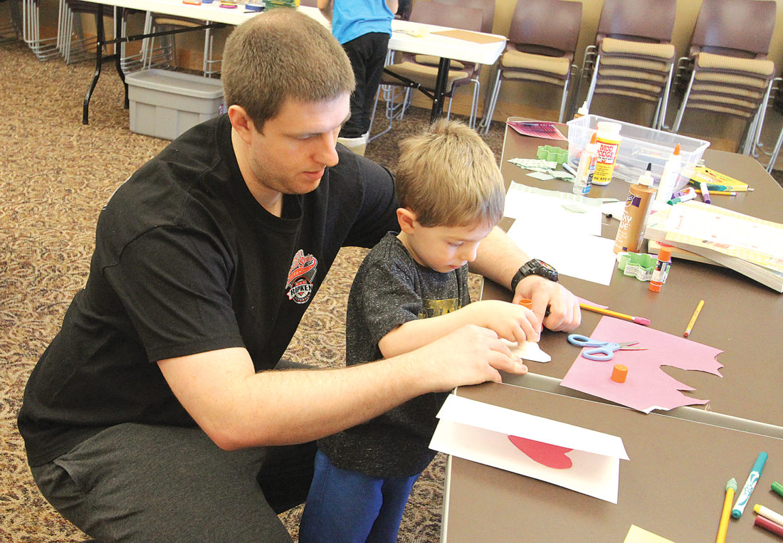 "Photo by Deb Gau Nate McNett helped Kaysen McNett cut out a paper heart to glue on the front of a card he was making, during the ""Be Kind"" event at the Marshall-Lyon County Library on Saturday. The cards kids made at the event will be given to veterans."