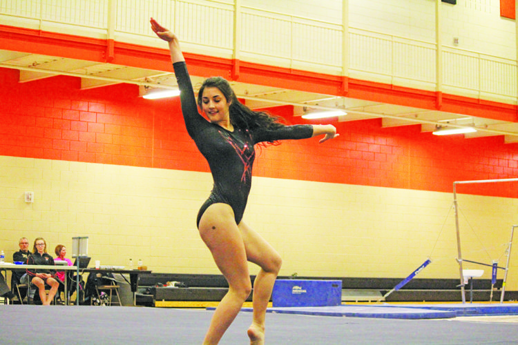 Photo by Sam Thiel  Marshall's Mikayla Chesley performs her floor exercise routine Monday night against Hendricks.