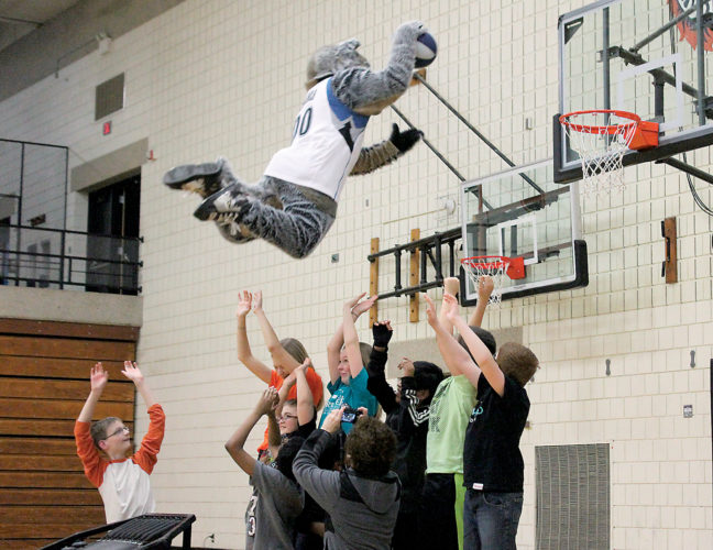 Photo by Mike Lamb Crunch, the Minnesota Timberwolves mascot, jumps over a group of Marshall Middle School student and teachers  during a dunk show Thursday afternoon.  Crunch entertained the students with games and dance moves.