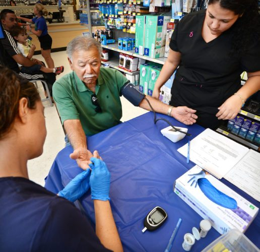 Alvin Arakaki gets his blood pressure read by Maui Medical Group medical assistant Stephanie Martinez (right) and his blood sugar checked by Maui naturopathic doctor Teri Jackson. The Maui News / MATTHEW THAYER photo The Maui News / MATTHEW THAYER photo
