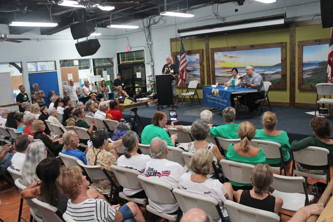 County Council Member Don Couch (on stage with microphone) and challenger Kelly King address the crowd during a Kihei Community Association candidate forum Tuesday night. They are seeking the South Maui council residency seat. The forum featured six candidates from the Upcountry, South Maui and Wailuku-Waihee-Waikapu residency races. The Maui News / COLLEEN UECHI photo