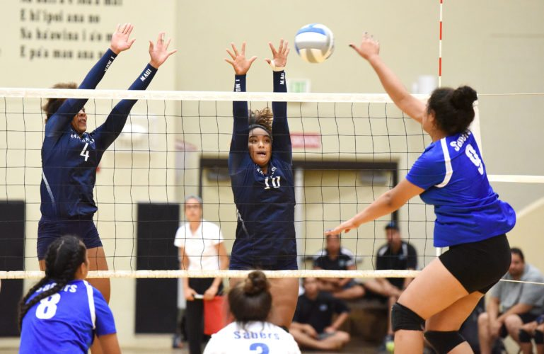Kimani Fernandez-Roy (left) and Hoala Alapai try to block a shot by Maui High's Anela Kalavi during the Warriors' 25-21, 25-20, 25-21 win over the Sabers on Thursday in a Maui Interscholastic League Division I tournament semifinal at the King Kekaulike Gym. The Maui News / MATTHEW THAYER photo