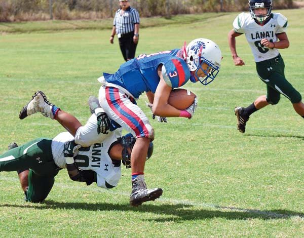 Seabury Hall's Kili Madrid Jr. tries to run through a tackle attempt by Lanai's Justin Belista in the second quarter Saturday.  The Maui News / MATTHEW THAYER photo