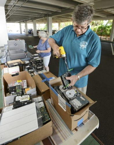 Maui County chief technology officer Jacob Verkerke uses a drill to unscrew brackets from the sides of hard drives while information security and privacy officer Karen Sherman feeds drives into a machine that either bends or pokes a series of holes in them to make them permanently unreadable Saturday at the county building in Wailuku.
