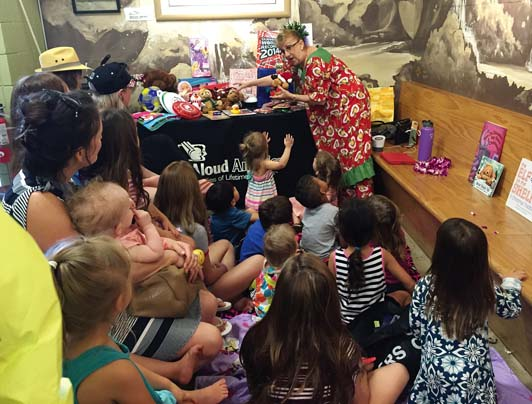 Read Aloud America Program Director Joanne Laird helps a child select her door prize at the Holiday Keiki Story Time.