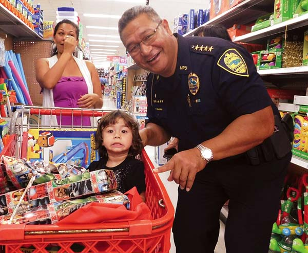 Police Chief Tivoli Faaumu helps 2-year-old Konner Vierra and his mother, Amanda, pick out toys at the Shop With a Cop event Saturday at Kmart.  The Maui News / LILA FUJIMOTO photo