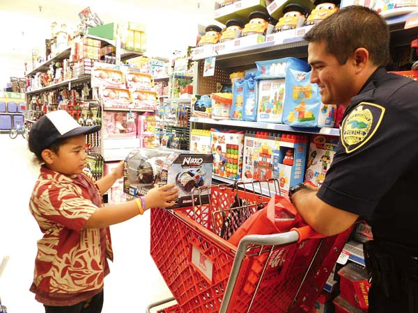 Eleven-year-old Cornelius Aveado shows a remote-control vehicle to officer Brandon Phillips.  The Maui News / LILA FUJIMOTO photo
