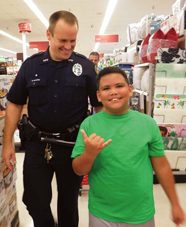 Eleven-year-old Jason Young leads the way with traffic investigator Ryan Ehlers at the Shop With a Cop event Saturday at Kmart.  The Maui News / LILA FUJIMOTO photo