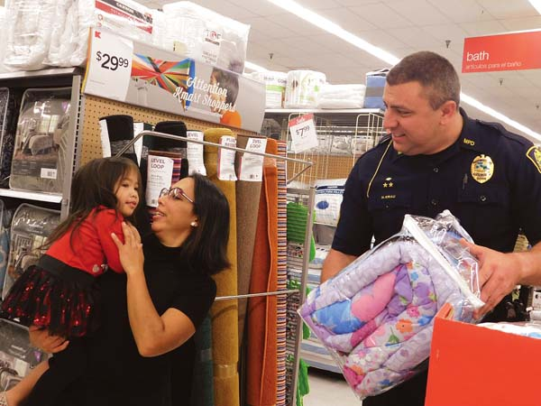 "DUI Task Force Sgt. Nick Krau hands a ""Frozen""-themed blanket to 2-year-old Kiyomi Sarmiento and mom Priscilla Felipe at the Shop With a Cop event Saturday at Kmart.  The Maui News / LILA FUJIMOTO photo"