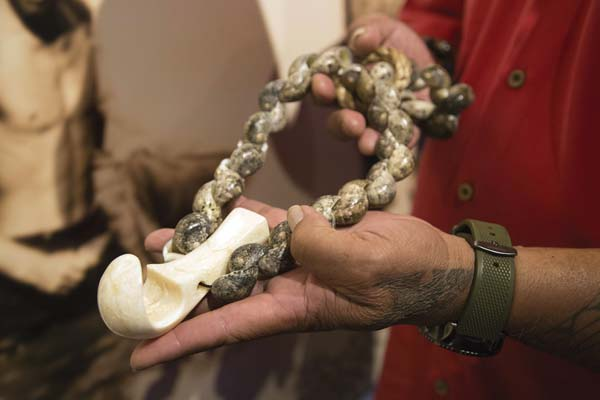 Kekai Kapu, cultural director at the Maui Ocean Center, presents a niho lei palaoa that has been in his family for many generations. The whale toothed necklace was the second most valuable artifact an alii (royal chief) could possess as it represented power, strength, and served as a vessel for mana, a spiritual energy from the gods and their ancestors. The necklace was made with the braided human hair of an ancestor and the pendant carved from a whale tooth into the shape of a tongue, signifying that the bearer speaks with authority. Maui Ocean Center photo