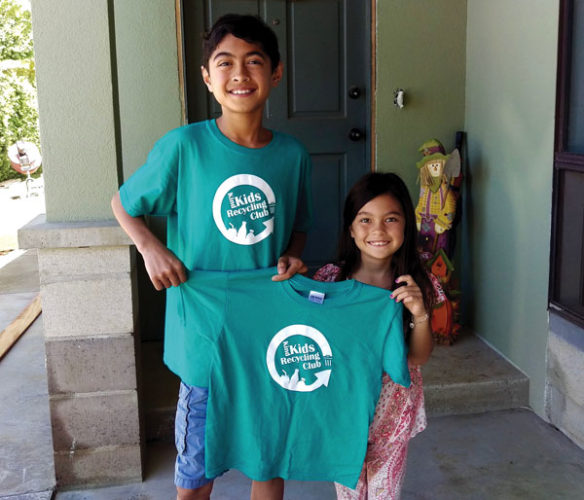 """DJ Metzler (left) presents an official Kind Kids Recycling Club T-shirt to 7-year-old Peyton Butcher. Club members receive a T-shirt when they complete three """"Pay it Forward"""" good deeds and three recycling runs."""