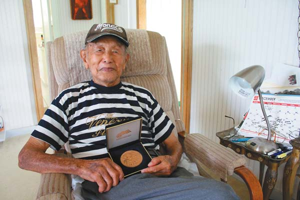 "Military Intelligence Service veteran Tom Yamada poses with the Congressional Gold Medal, awarded to Japanese-American veterans in 2011, in his Wailuku home. ""MIS: America's Secret Weapon,"" is on display at the Nisei Veterans Memorial Center until the end of January. The Maui News / COLLEEN UECHI photo"