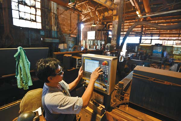 Millwright Ronnie Guzman punches instructions into the control panel of a machine after cutting parts out of 1 1/4-inch steel for Hawaiian Commercial & Sugar Co.'s mill.  The Maui News / MATTHEW THAYER photo
