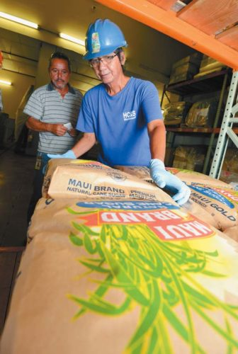Hawaiian Commercial & Sugar Co. crew member Mario Pisalvo lifts a 50-pound bag of Maui Brand sugar for Michael Fernandez at Puunene Mill.  The Maui News / MATTHEW THAYER photo