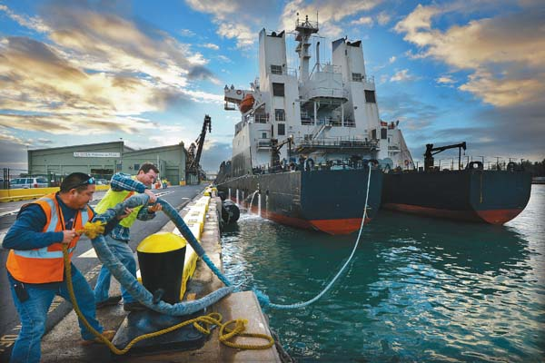 Stevedores Leighton Emura (left) and Keoki Brown cast off the Moku Pahu's mooring lines while readying the sugar ship to depart Kahului Harbor with its last load of unprocessed sugar bound for California.  The Maui News / MATTHEW THAYER photo