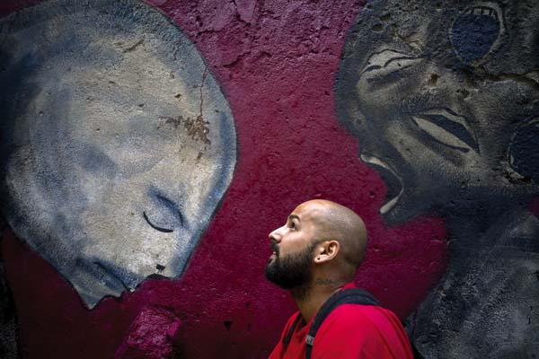 Graffiti artist Yulier Rodriguez Perez poses with one of his works, painted on a wall in Old Havana, Cuba. Three years ago, the whimsical designs of the 27-year-old artist with the signature Yulier P. began to appear on walls in Havana where graffiti is rare.    AP photo