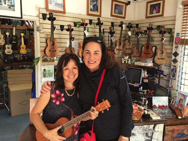 Mele Ukulele owner Cheryl Rock (left) is shown with Realtors Association of Maui member Moana Andersen in the showroom of the Wailuku music store.