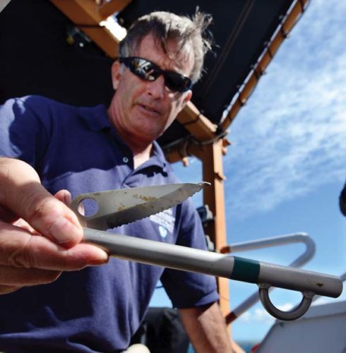 Ed Lyman, large whale entanglement response coordinator with the Hawaiian Islands Humpback Whale National Marine Sanctuary, displays a flying knife. The cutting tool is serrated on its inside edge, making it suited to removing netting or debris from an entangled whale.  The Maui News MATTHEW THAYER photo