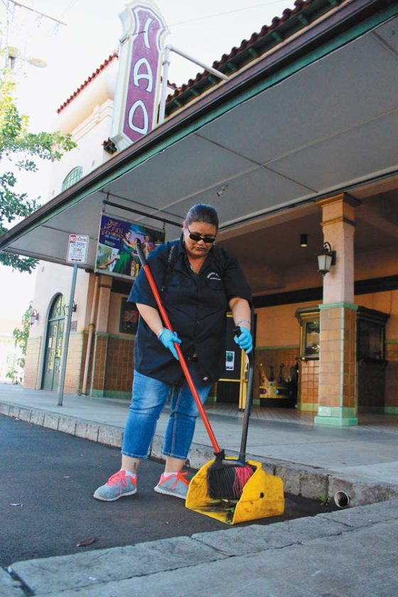 Rosalind Toyama sweeps leaves in front of Iao Theater early Friday as part of Wailuku town's Clean & Safe program. The program gives street-cleaning jobs to Mental Health Kokua clients and aims to make the streets safer through regular neighborhood checks. The Maui News / COLLEEN UECHI photo