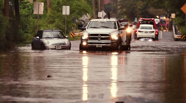 Stranded cars are towed from the flooded intersection of South Kihei Road and Kaonoulu Street on March 7, the latest flood episode in the area, which the county hopes to relieve through a South Maui Drainage Master plan.  The Maui News / MATTHEW THAYER photo