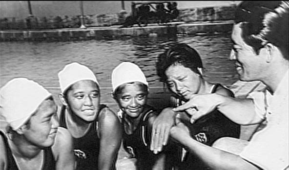 Coach Soichi Sakamoto teaches stroke technique to his swimmers.