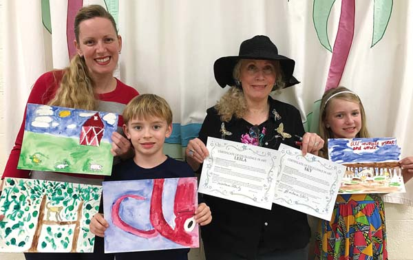 Kealani Schmitt (from left), Skyler Schmitt, Barbara Steinberg and Leila Schmitt hold up their best art with certificates of excellence presented by Steinberg.