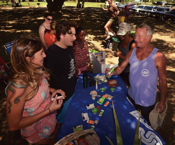 University of Hawaii Maui College Student Ohana for Sustainability President Alicia Wood (from left), member Dwight Baldwin and secretary Lyu Burdette discuss sunscreen with Kihei's Alan Pelzer. -- The Maui News / MATTHEW THAYER photo