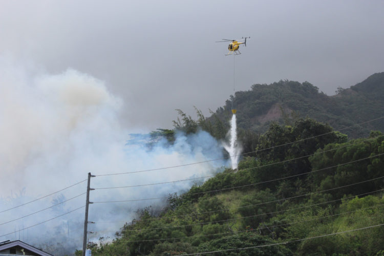 A Maui Fire Department helicopter drops water on a brush fire burning off Mokuhau Road in Happy Valley on Sunday afternoon. • The Maui News / COLLEEN UECHI photo