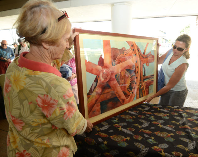 "Haiku artist Christine Waara (right) hands her sugar-mill-inspired watercolor titled ""Change Gears"" to Art Maui co-show Chair Mary Ann Leigh.  • The Maui News / MATTHEW THAYER photo"