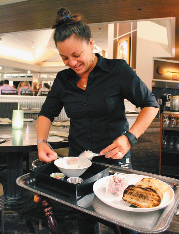Server Tia D'Ambrosia does steak tartare in a tableside presentation.