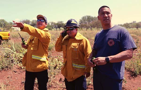 Assistant Fire Chief David Thyne (from left), training Capt. Rylan Yatsushiro and Battalion Chief Amos Lonokailua-Hewett watch a wildland live-fire training exercise Wednesday morning in north Kihei. The Maui News / CHRIS SUGIDONO photo