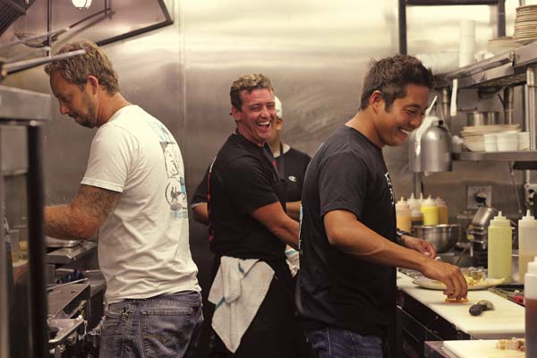 """Chefs and co-owners of Three's Bar & Grill Jaron Blosser (from left), Cody Christopher and Travis Morrin laugh in the kitchen of their Kihei restaurant Tuesday. Six months after a fire damaged their restaurant, Three's was selected to feature on Food Network's """"Diners, Drive-ins and Dives."""" Host Guy Fieri visited earlier this month to film with several Maui restaurants, including Three's. Episode dates have not yet been announced. The Maui News / COLLEEN UECHI photo"""