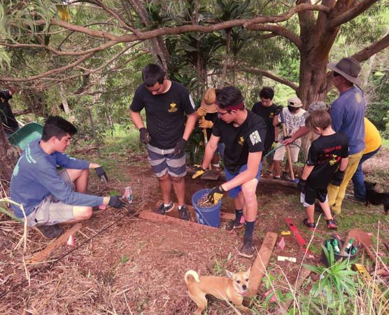 Aolama Chow (left) teaches his crew of 35 volunteers, Scouts of Troop 100, to build steps with proper rise, depth and width.