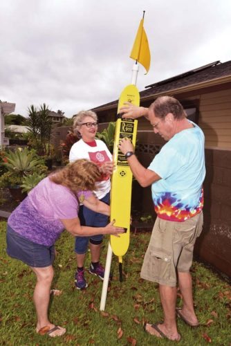 Rotary Club of Kihei-Wailea members Patty Hemmen, MaryMargaret Baker and Dave Hemmen practice setting up one of the rescue tubes the club is scheduled to place at South Maui County beaches next month. Club members were slated to put out 28 of the tubes Saturday, but the work detail was postponed by heavy rains. -- The Maui News / MATTHEW THAYER photo