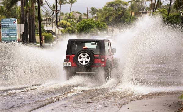A motorist on South Kihei Road splashes through the Auhana Road intersection by the Kalama Park volleyball courts after a band of heavy showers passed over the area Saturday morning. A Kona low-pressure weather system is expected to bring more rain through Monday, according to the National Weather Service. -- he Maui News / MATTHEW THAYER photo