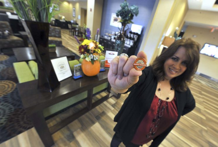 -Messenger photo by Hans Madsen  Amy VonBank, general manager of the Holiday Inn Express in Fort Dodge, displays a pin earned as part of a recent award.