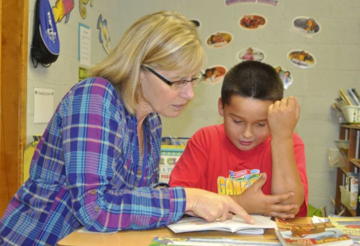 -Messenger photo by Chad Thompson  Jean Black, business manager at Community Christian School in Fort Dodge, left, works with second grader Israel Alvarez on his reading skills at the school recently. Black began her role as business manager on Aug. 1. Her duties range from approving bills to meeting with prospective parents, she said.
