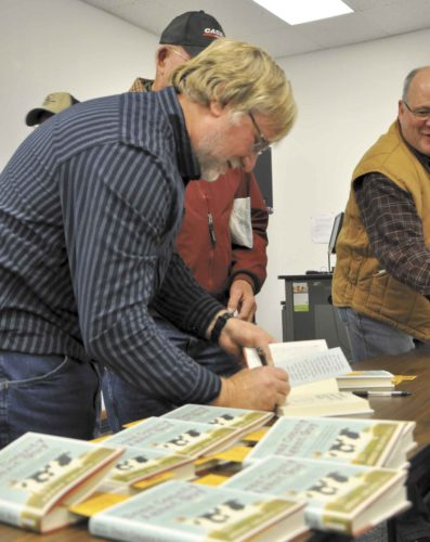 "-Messenger photo by Joe Sutter Jerry Nelson, of Volga, South Dakota, signs copies of his book, ""Dear County Agent Guy,"" during the Farm News Ag Show Wednesday afternoon."