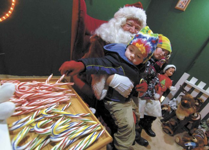 "-Messenger file photo by Hans Madsen  Declan Estes, then 2, of Algona, tries to decide on the traditional red and white candy cane or one of the multi-colored ones during a visit to the Kiwanis Christmasland display in Humboldt in 2014. His sister, Sofia Estes, then 3, examines her own candy cane. Dave ""Santa"" Lee, was chairman of the group's display committee."