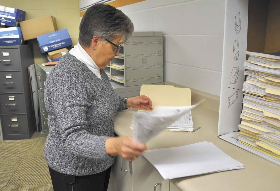 -Messenger photo by Peter Kaspari  Marcia Vote, a civil clerk with the Webster County Sheriff's Department, goes through some old files in the office. Vote is retiring at the end of the month after nearly 20 years with the Sheriff's Department.