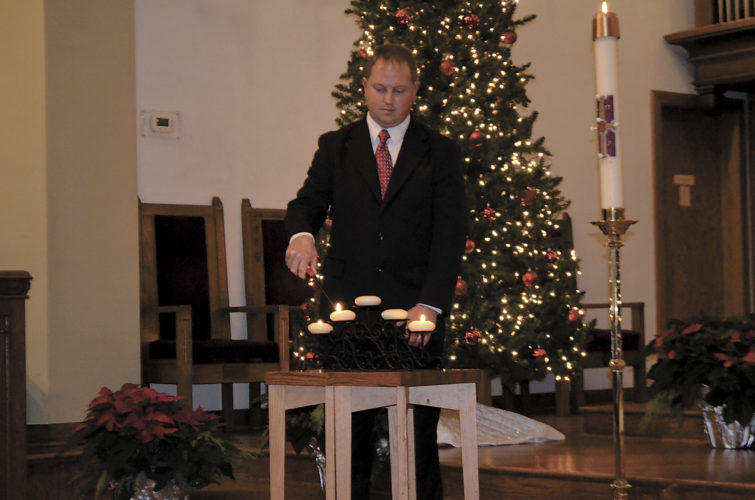 -Messenger photo by Chad Thompson  Rob Gunderson lights the candles during a service of remembrance held Sunday afternoon at Saint Olaf Church, 239 North 11th St. More than 400 people attended.
