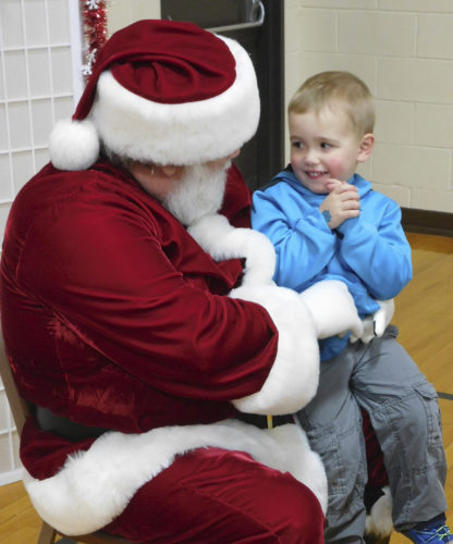 -Messenger photo by Deanna Meyer Christian Lamphier, 2, tells Santa that he wants a dinosaur and a combine for Christmas Sunday during the Hometown Christmas event at the Manson Area Community Center.