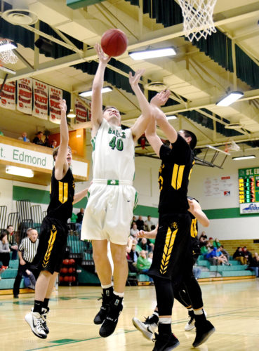 Messenger photo by Britt Kudla  Jake Heidenreich of St. Edmond shoots around two Bishop Garrigan defenders in the Gael gym.