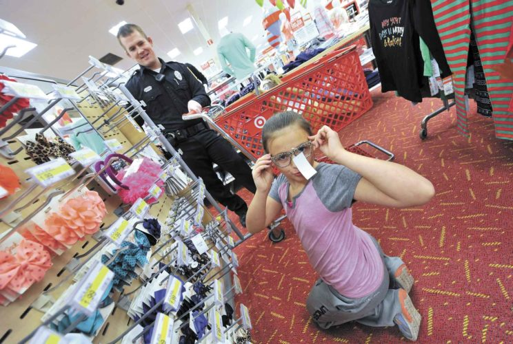 -Messenger photo by Hans Madsen Fort Dodge Police Officer Matt Burns watches as Cassie Welch, 10, of Fort Dodge, tries on a pair of stylish glasses Tuesday evening at the Fort Dodge Target Store during the annual Santa Cops event. The young aspiring fashion consultant had purchased many other items for her family.