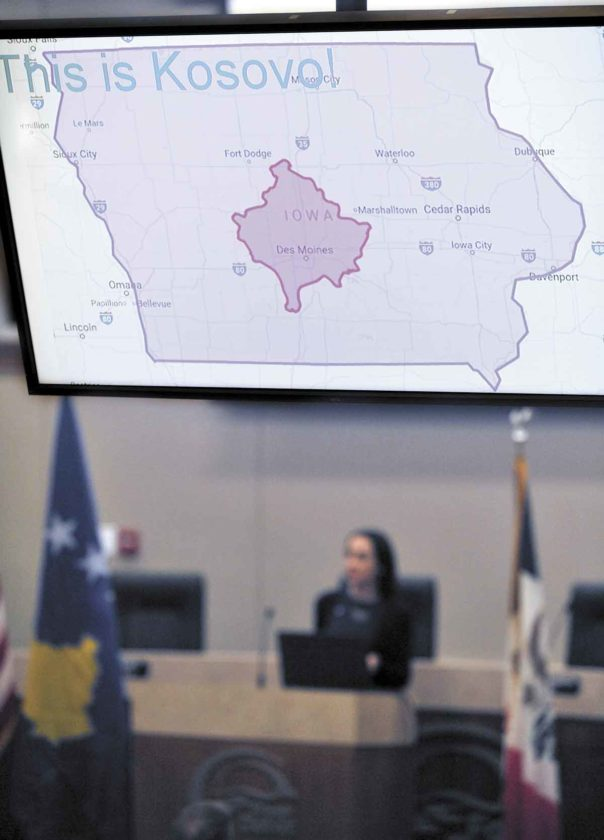 -Messenger photo by Hans Madsen  With a map showing Kosovo in relationship to Iowa on the projector screens, Jehona Gjurgjeala, director of Camp TOKA in Kosovo, speaks Wednesday night at the Fort Dodge Municipal Building.